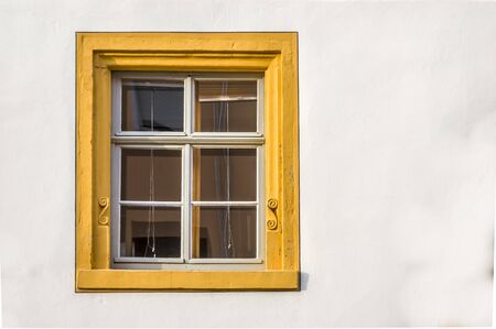 Window of a restored half-timbered house partly plastered with sandstone framing, decorated with yellow colour