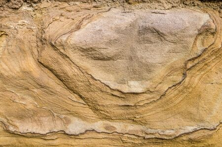 Sandstone wall, sandstone with artistic patterns hatching relief-like shapes on the surface, detail shot