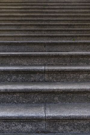 Section of a granite staircase with many steps as background