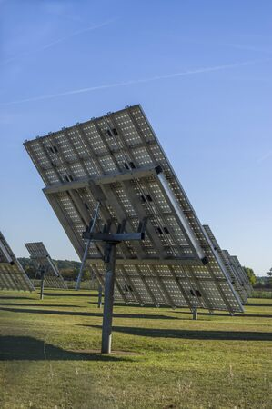 Solar system, solar power plant with trackable elements in sunshine, Side view with servomotor