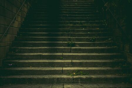 Wide staircase in a park made of natural stone with a handrail made of rusted steel in the dim light with a creepy and scary aura like in a thriller Stock fotó