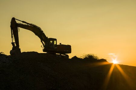 Construction site idyll, excavator at construction site in sunset with sunstone, silhouette