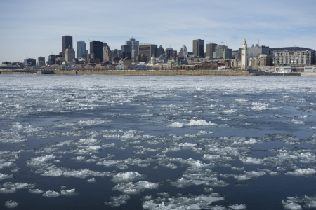 Montreal Skyline in winter, with chunks of ice floating on the Saint-lawrence.