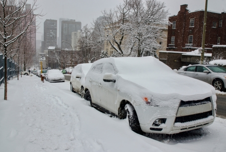 Cars buried by the snow with skyscrapers in the distance, Montreal Stockfoto