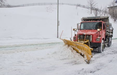 Snow plough clearing road in winter storm