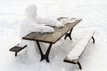 Lonely snow man sitting at picnic table in winter Banco de Imagens