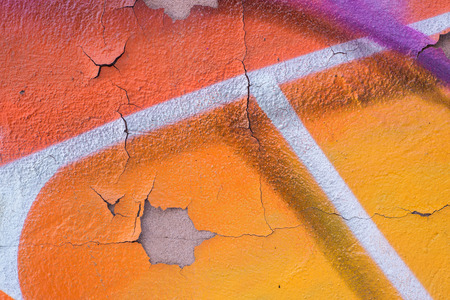 ornage: Closeup of a peeling and cracked wall with ornage, violet, and white spray drawings