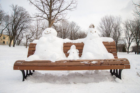 Family of snowman on a bench : father mother and kid Stock Photo