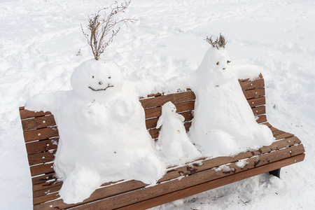 mother on bench: Family of snowman on a bench : father mother and kid Stock Photo
