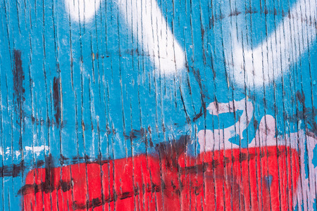 tagged: Vertical Lines of Peeling blue paint on wooden wall, with red and white spray paint markings