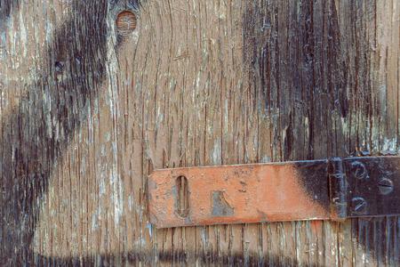 hinge: Old wooden door with rusty red hinge