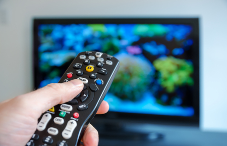 channel surfing: Watching tv and using remote control Stock Photo