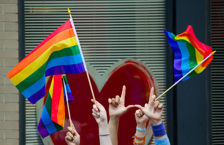 gay symbol: Hands waving gay flags in front of a big red heart Stock Photo