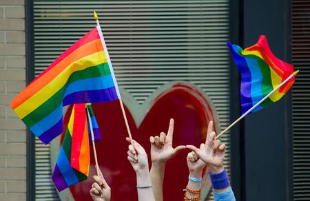 Las manos con banderas de los homosexuales frente a un corazón rojo grande
