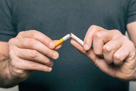 Dejar de fumar - mano masculina aplastamiento de cigarrillos