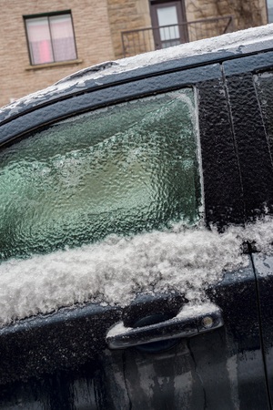iciness: Montreal, CA, 29th February 2016. Car handle and window are covered with ice after freezing rain.
