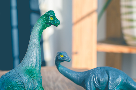 Close-up of two plastic dinosaur toy with retro vintage effect