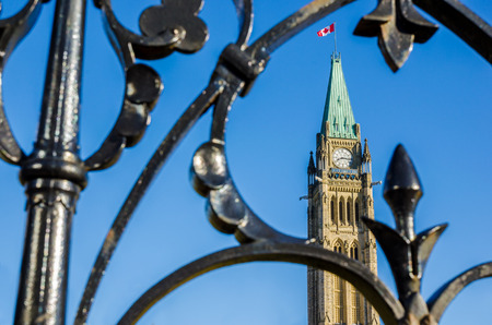 low angles: Canadian Parliament Peace Tower hrough the front fence in Ottawa