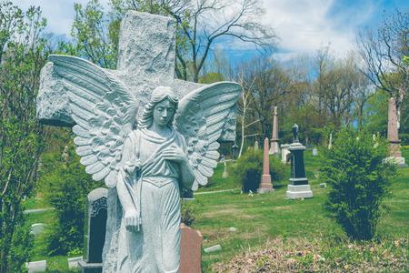 Angelo davanti a una statua di croce in un cimitero, con un effetto vintage.