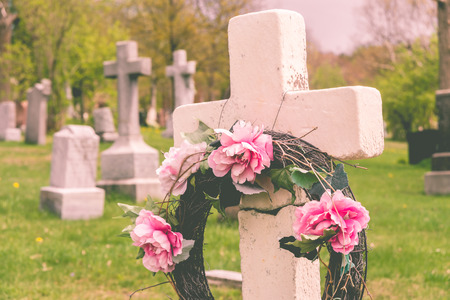 gravesite: Funeral wreath with pink flower on a cross, in a cemetary, with a vintage filter.