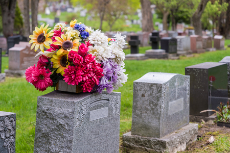 Flowers on a tombstone in a cemetary with headstones in the background 免版税图像