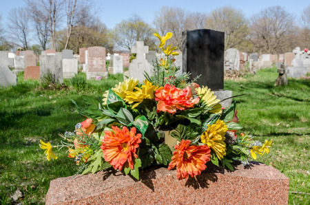 hundreds: Flowers on a tombstone in a cemetary with hundreds of tombstones in the background