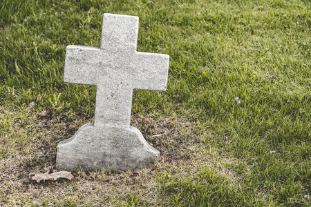 empty tomb: Cross shaped blank Headstone in a cemetery Stock Photo