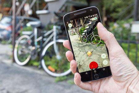 モントリオール、カリフォルニア - 2016 年 7 月 27 日: ポケモン移動をスマート フォンで遊ぶ男のクローズ アップ。2016 年 7 月にリリースされた仮想