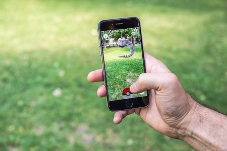 ar: Montreal, CA - July 22, 2016: An Iphone user is playing Pokemon Go, a mobile game developed by Niantic