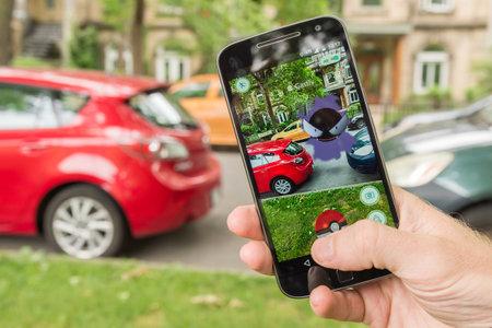 モントリオール、カリフォルニア - 2016 年 7 月 28 日: ポケモン移動をスマート フォンで遊ぶ男のクローズ アップ。2016 年 7 月にリリースされた仮想