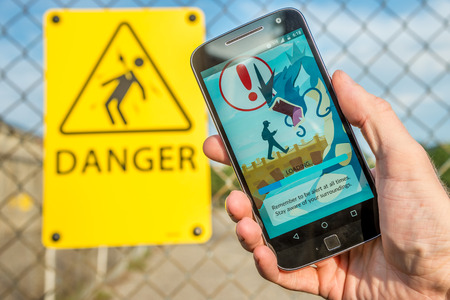 videogame: Montreal, CA - July 27, 2016: Closeup of the loading screen of the videogame Pokemon Go remembering players to be alert. Pokemon Go is a virtual reality game released in July 2016.