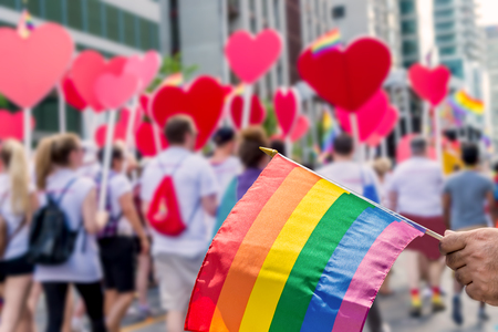 Rainbow flag floating in front of blurred gay pride participants holding hearts