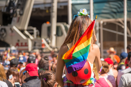 spectator: A female spectator with a rainbow flag is watching the gay pride parade in Toronto, Canada.