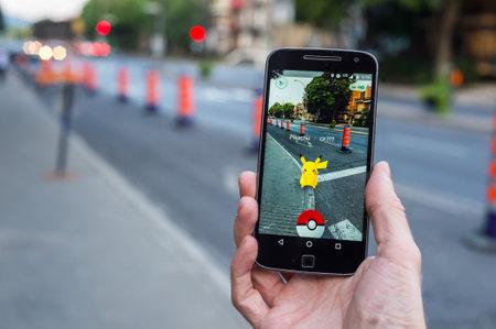 モントリオール、カリフォルニア - 2016 年 8 月 11 日: ポケモン移動をスマート フォンで遊ぶ男のクローズ アップ。2016 年 7 月にリリースされた仮想
