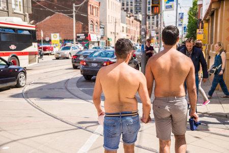 hombres gays: Toronto, Canadá - 3 de julio 2016: Dos hombres homosexuales sin camisa están caminando juntos y la celebración de sus manos