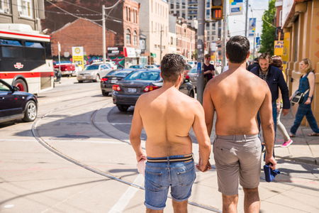 Toronto, Canada - July 3, 2016: Two shirtless gay men are walking together and holding their hands