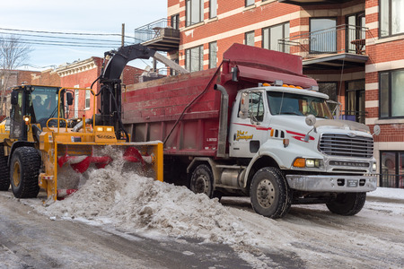 dumps: Montreal, CA, 5th March 2016. A snow thrower is blowing snow into a dump truck after snow storm.