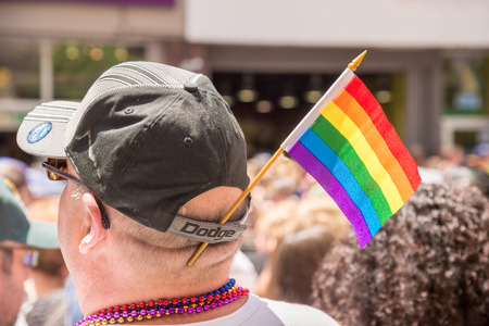 spectator: Toronto, Canada - July 3, 2016: A male spectator is watching the gay pride parade with a gay rainbow flag attached to his cap