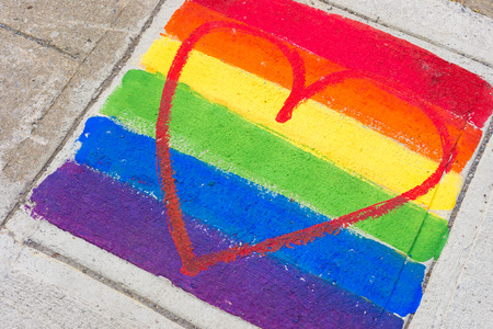 Gay rainbow flag and red heart painted on a sidewalk Stockfoto
