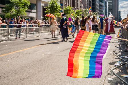 トロントのゲイプライド参加者がぼやけて虹旗の前に浮