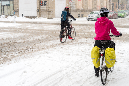 snow storm: Montreal, CA, 7th March 2016. Two people riding bikes during snow storm