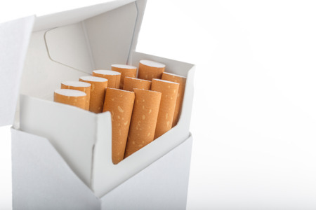 standardised: Open pack of cigarettes stands vertically over white background