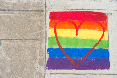 Gay rainbow flag and red heart painted on a sidewalk Stock Photo
