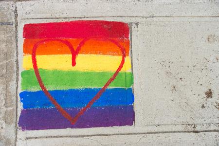 게이 무지개 깃발과 붉은 마음 보도에 그려진