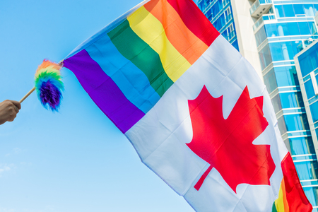 Montreal, CA, 16th August 2015. Canadian gay rainbow flag waving over blue sky during Montreal Pride parade.