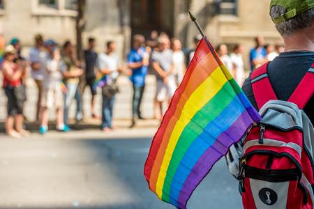 男性の観客は、モントリオールで 2015 ゲイプライド パレードでゲイの虹色の旗を保持しています。