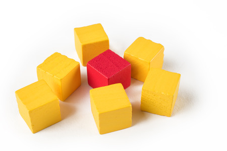 differentiation: One blue wooden mini block among red blocks symbolizing exclusion, difference, or bullying Stock Photo