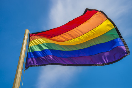 wave equality: Gay rainbow flags waving over blue sky background