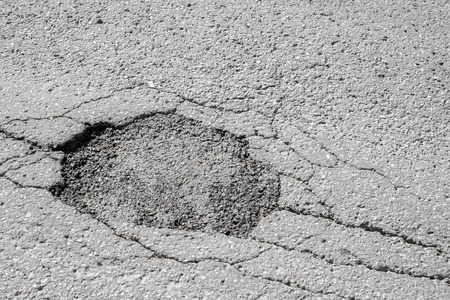 patched: Large patched deep pothole in Montreal street, Canada.