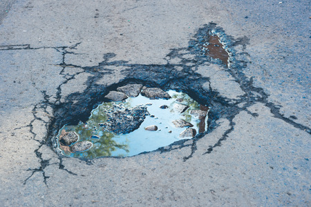 Large deep pothole with blue sky reflection and faded effect in Montreal street, Canada.